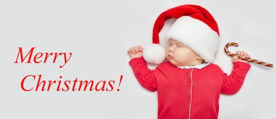 "Christmas card or banner with a newborn sleeping baby in a Santa Claus hat, red-and-white clothes and a Candy Сane in a small hand. The inscription ""Merry Christmas!"""