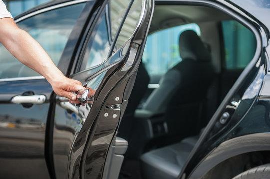 Close up man opens car's door.