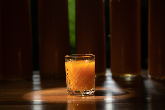 alcoholic cocktail in a shot glass on a totally wooden background: homemade bitter berry tincture with a buckthorn