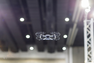 UAV drone copter flying with digital camera.Drone with high resolution digital camera. Flying camera take a photo and video.The drone with professional camera takes pictures of in the hall (indoor).