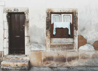 A weathered old facade of an antique building in Lisbon, Portugal, with the metal door and a single window with a drying jacket thrown over the shutters, the wall with flaked plaster