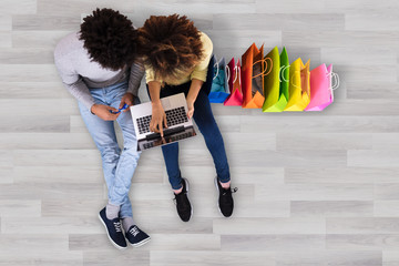 Young Couple Using Laptop With Colorful Shopping Bags