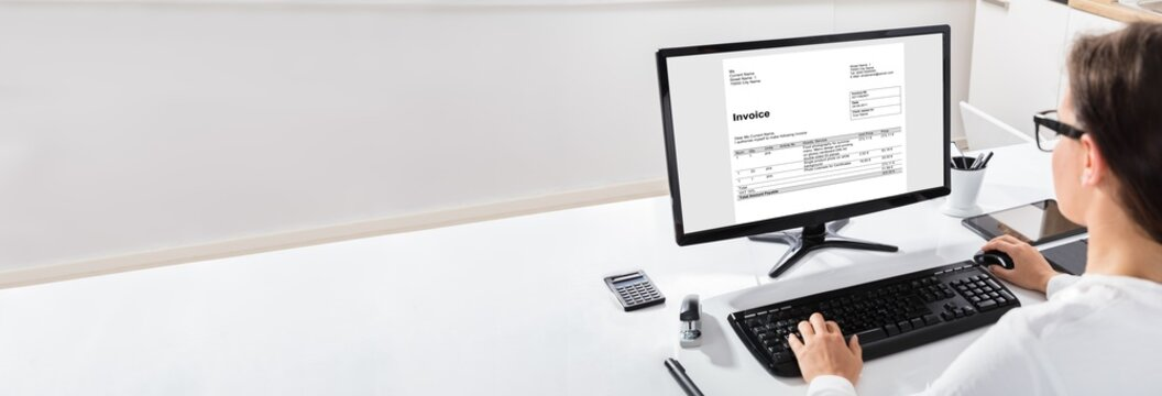 Woman Using The Computer With Invoice Form On Screen