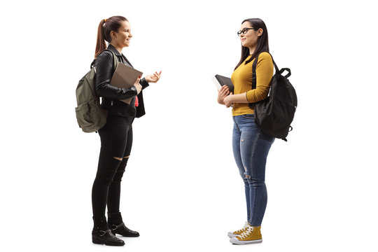 Two female students with books and backpacks having a conversation