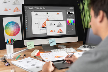 Graphic designer drawing sketches logo design. Fotobehang