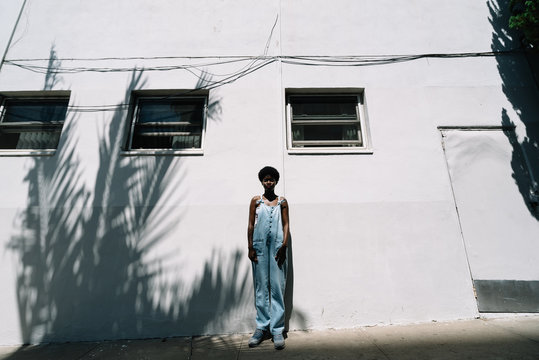 Portrait of woman wearing coveralls standing in front of building