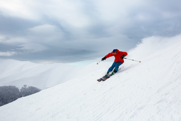 Fototapete - A skier in the red jacket is riding fast.