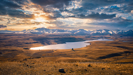 Lake Alexandrina surrounded by tawny tussock and snowy peaks, hidden gem in the Mackenzie region, South Island, New Zealand