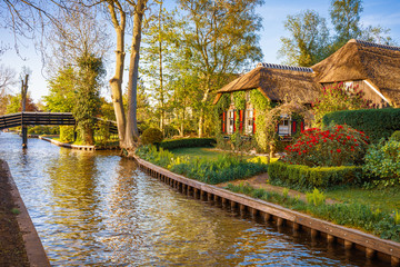 Lovely landscape with canal and picturesque houses with red shutters, Giethoorn, Netherlands