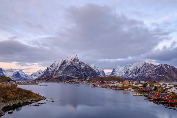 Reine, snow covered mountains in the background and the fishing cabins Rorbu in the foreground, Lofoten Islands, Norway