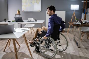 Businessman Sitting On Wheelchair In Office