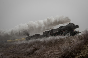 Two vintage steam locomotives running back to back on a railroad embankment. Steam locomotives in winter.
