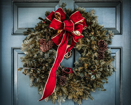 Christmas wreath with large red bow trimmed in gold hanging on old wooden blue door