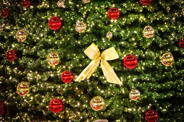 Christmas tree decoration details. Close-up Christmas and New Year baubles on a Christmas tree. Colorful balls and bow
