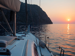 Meet the sunset in the Bay on Board the yacht, a romantic evening at sea. Boat trip on a yacht under sail.