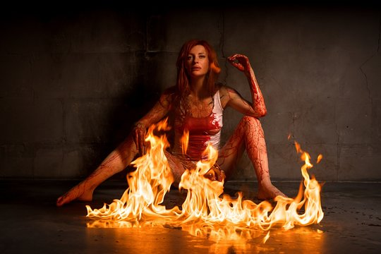 Red-haired nude girl in blood and fire view
