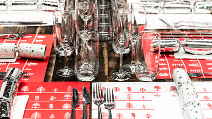 A table set up for Christmas dinner with placemats, cutlery, glasses and Christmas crackers