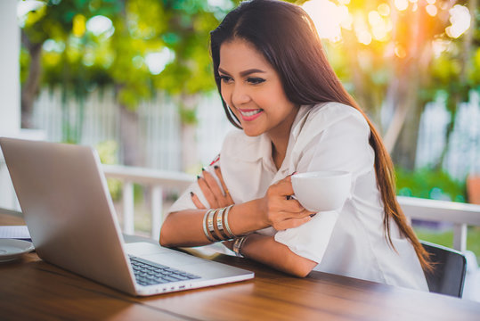 Happy smile Asian business woman using laptop at cafe, Vacation businesswoman working at home, Beautiful hipster girl blogger thinking content with notebook computer, Freelance business people in Asia
