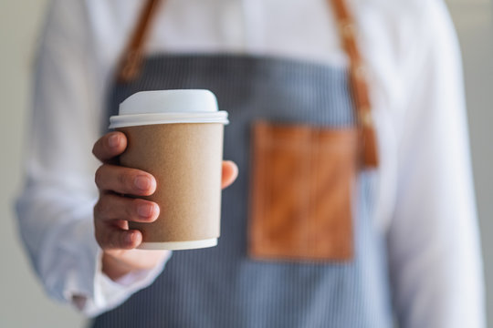 A waitress holding and serving a paper cup of hot coffee in cafe