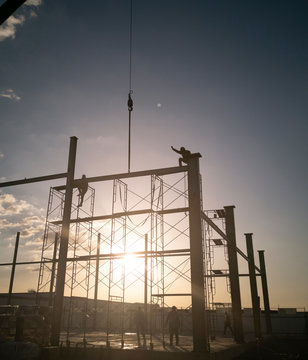 welder is working on top of column, process before install metal sheet siding, connecting plate on ground, photo is Flare filter, picture is portrait style