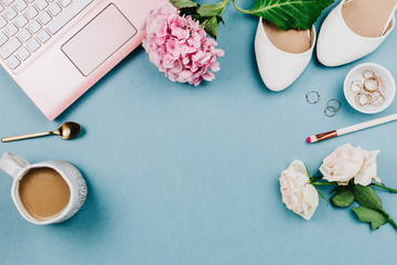 Beautiful feminine flatlay of pink laptop and woman's white shoes, jewerly and flowers on blue, selective focus