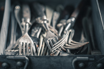 Closeup of stack of forks in a metal box