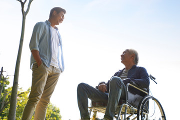 asian son talking to wheelchair bound father