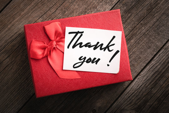 Top view red gift box and label with the words thank you on wooden background: concept of expressing gratitude and thanks