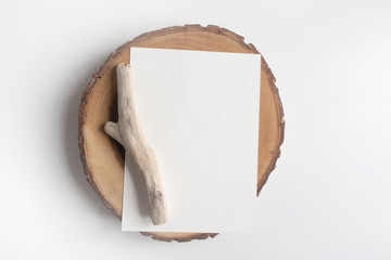 Mock up of postcard on wooden cut tree section on white table. Boho design of postcard on white table with copy space for your image or text