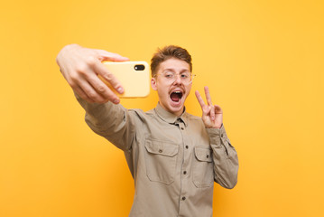 Happy young man in glasses and shirt is taking a selfie on a yellow background, looking into the camera of a smartphone, smiling and showing a gesture of peace. Nerd with mustache makes selfie