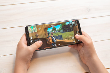 Sarajevo, Bosnia and Herzegovina - November 30, 2019: Garena Free Fire video game on Samsung Galaxy S9 plus smarthone in kid hands close-up