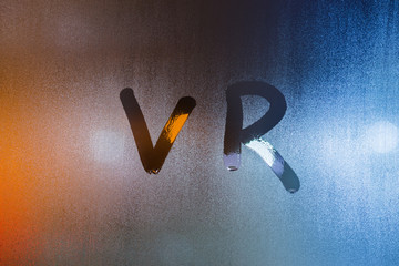 the word vr - virtual reality - written by finger on wet glass with blurred lights in background