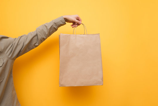 Background. A man in a shirt holds a paper shopping bag. Crafting a shopping bag in a man's hand. Replacing plastic bag. Eco package concept. Copy space