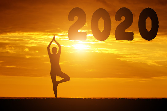 Silhouette of the number 2020 and a girl doing yoga on the background of the sunset sky. New Year concept