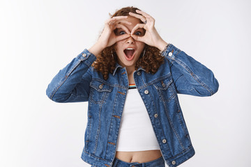 Speechless excited astonished emotive cute curly-haired young girl drop jaw gasping amazed make goggles fingers look through binocular-shaped gesture amused surprised, white background