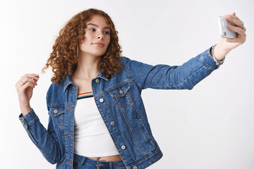 Stylish attractive confident modern young redhead girl roll curl finger extend hand hold smartphone take selfie strike cool glamour pose post picture online renew personal profile internet