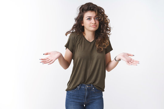 How should I know. Portrait perplexed clueless young unbothered attractive caucasian woman shrugging hands spread sideways cannot answer, not know, standing confused white background