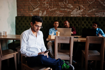 Group of four south asian men's posed at business meeting in cafe. Indians work with laptops...