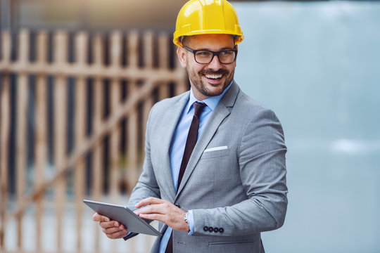 Handsome caucasian happy architect in gray suit and with yellow helmet on head using tablet while standing on construction site and looking away.