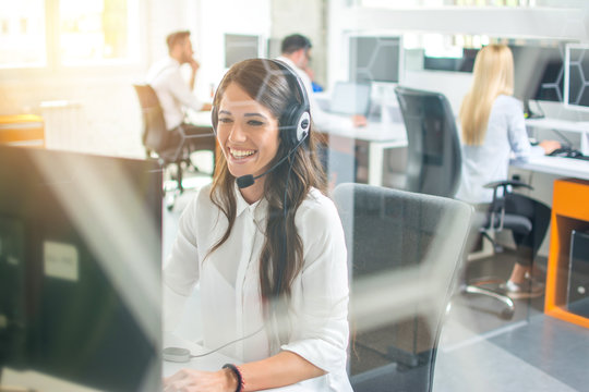 Friendly female call center operator working in office