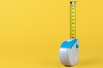 Measuring tape isolated over yellow bakground. Carpenter and Construct concept.
