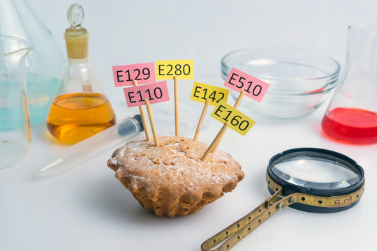 A cupcake decorated with name plates of additives E, test tubes and a magnifier stand nearby. Food laboratory. Close up on a white table.