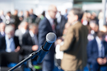 Business conference or corporate presentation. Microphone in focus against blurred audience.