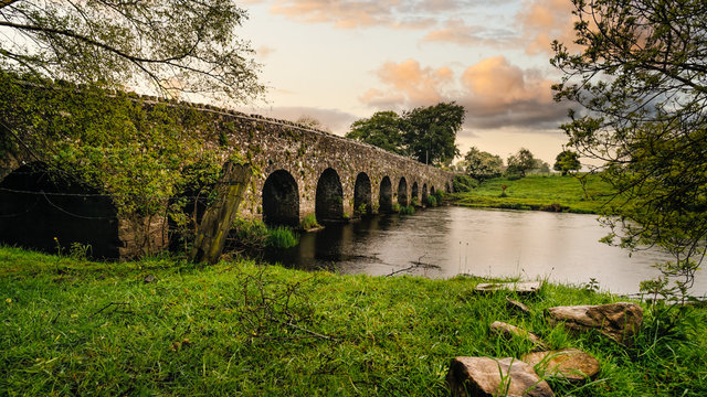 Old 12th century stone arch bridge over a river, rocks on first plane. Green fields and trees. Dramatic sky sunset. Count Meath, Ireland