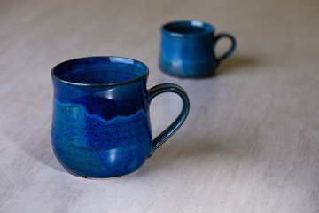 Two blue handmade empty mugs over grey background.
