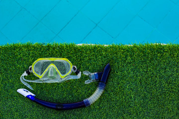 snorkeling gear mask and tube elementary level equipment water activity life style hobby concept wallpaper pattern picture with green grass and swimming pool blue water background empty copy space