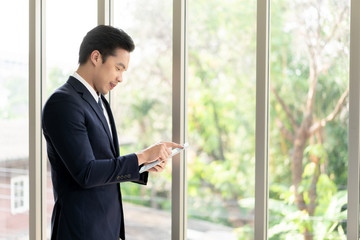 Young Businessman Smiling while using Digital Tablet.