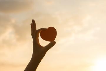 Silhouette broken heart,close up woman hand holding broken heart in the park.