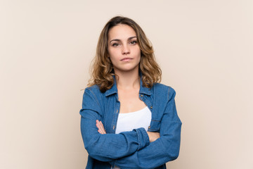 Young blonde woman over isolated background keeping arms crossed