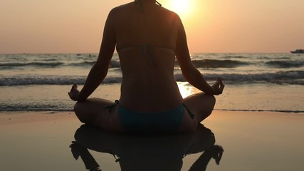 Wall Mural - meditation and yoga, camera moving up, relaxation and breathing exercises, silhouette of woman on the beach